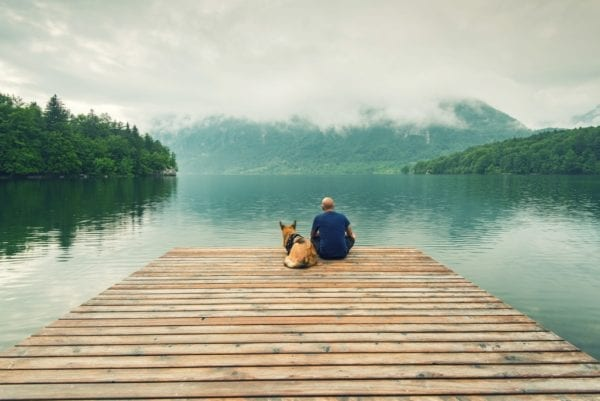 Man with dog sitting at wooden pier at Bohinj Lake, SLovenia.