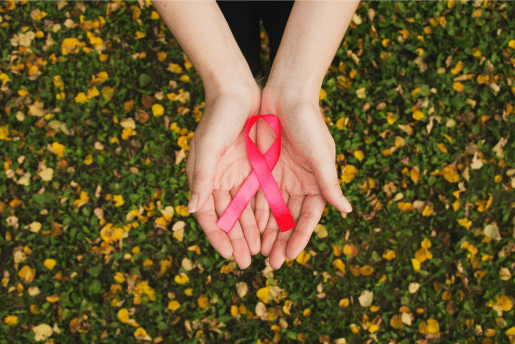 hands in front of a field of yellow flowers holding the pink breast cancer awareness ribbon